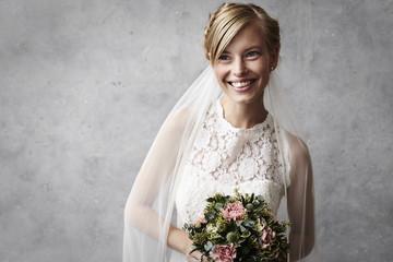 Beautiful blond bride holding flowers