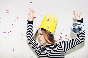 Birthday party, new year carnival. Young smiling woman on white background celebrating brightful event, wears stripped dress and yellow crown. Sparkling confetti, having fun, dancing, laugh, smile.