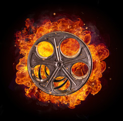 Film reel in fire, isolated on black background
