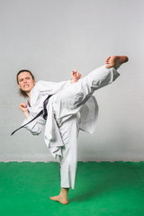 Young Woman Practicing with Kicks in Karate Martial Art