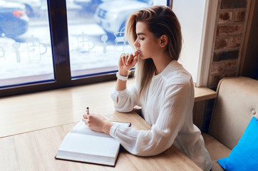 Young blond girl making notes in a notebook while sitting at the table