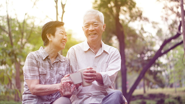 Healthy Asian senior couple drinking coffee in morning park together