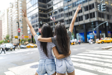 USA, New York City, back view of two young women in Manhattan having fun