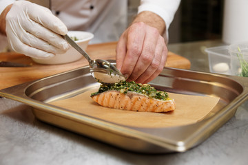 Chef is putting herbal sauce on grilled salmon