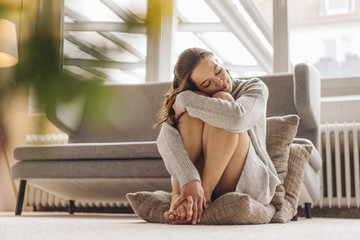Woman with closed eyes sitting on cushion on floor
