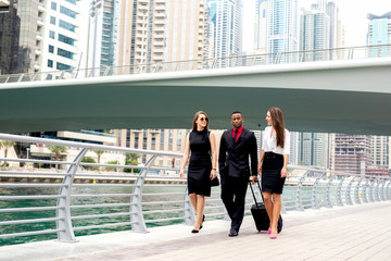 Three people heading to meeting walking down street discussing plans.