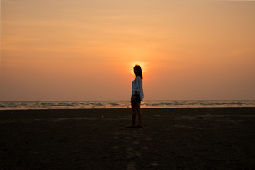 silhouette standing on the beach with sunset background
