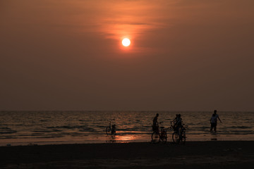 silhouette people playing on beach in the sea on sunset background