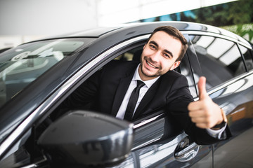 Businessman smiling at camera showing thumbs up in his car