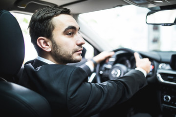 Close-up of man hands holding steering wheel while driving car