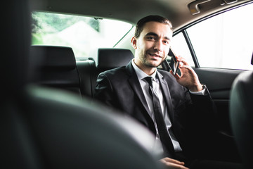 Businessman on call in car, smiling