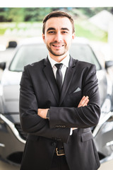 relaxed young businessman or salesman with hands crossed in front of car