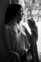 young woman by the window portrait in bw