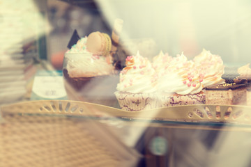 Cupcakes with vanilla cream on showcase in cafe under glass. Shallow depth of field. Toned.