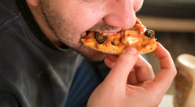 Man eating a slice of pizza