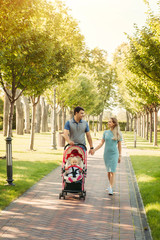 Young nice couple walking with baby girl in carriage