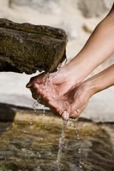 mains de femme prenant de l'eau de source naturelle