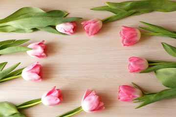 Spring tulips on the wooden biege background