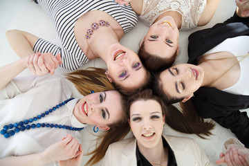 A group of joyful elegant girls lies in a circle, a top view, on a white background.