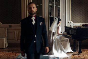elegant gorgeous bride playing the fortepiano and stylish handsome groom posing in rich old room. sensual look. unusual luxury wedding in retro style.
