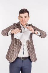 young businessman tearing paper in his hands on a white background.