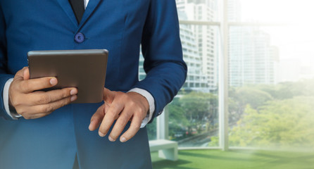 Businessman using digital tablet with modern building