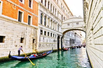 View of the Bridge of Sighs with Gondolas punted by gondoliers on the canal in Venice