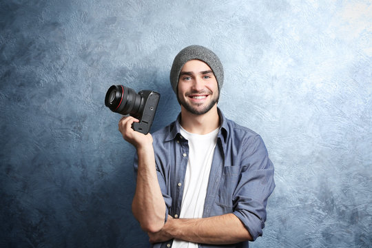 Handsome young photographer near grey textured wall