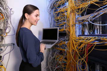Beautiful young engineer with laptop in server room