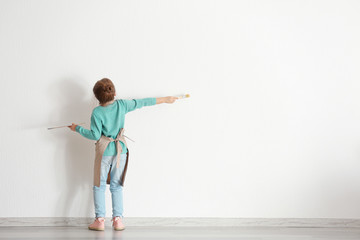 Cute little girl painting on wall in empty room