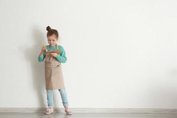 Cute little artist near light wall in empty room