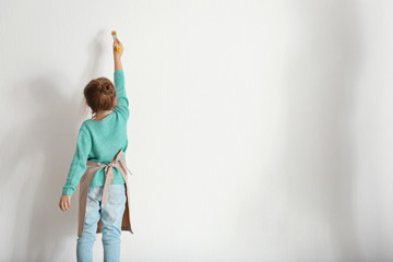 Cute little girl painting on light wall
