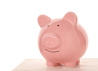 Pink ceramic piggy bank on wooden table