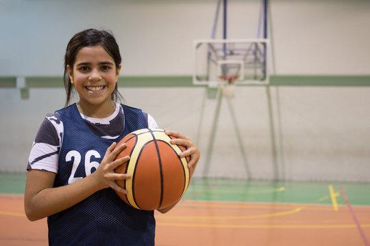 Mixed race girl holding basketball
