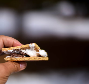 Camping dessert s'mores held by hand with a dark, blurred background