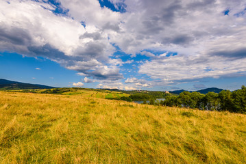 Picturesque rural landscape in summer day with amazing clouds on the sky. Pieniny mountains, Poland.
