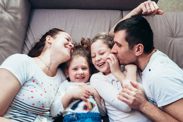 Happy family lying on the couch and laughing