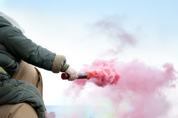 kid holding red smoke bomb detail outdoors