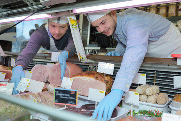 Male butchers reaching into counter