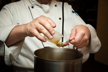 Culinary Person Measuring Olive Oil into Pot