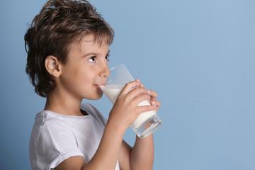 Cute kid drinking milk on blue background