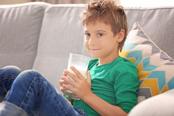 Cute kid holding glass of milk and sitting on sofa in the room