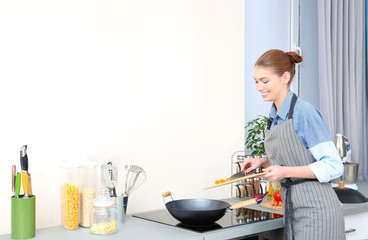 Woman putting vegetables in pan at kitchen