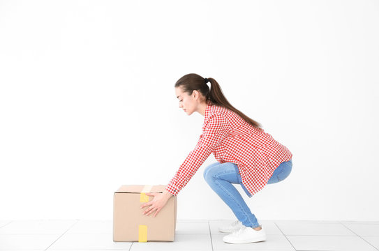 Posture concept. Young woman lifting heavy cardboard box against white wall background