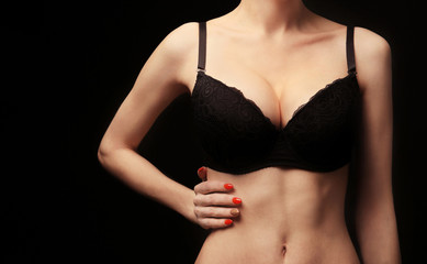 Young woman in bra on black background