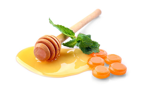 Cough drops with honey and mint on white background