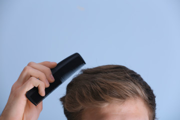 Handsome young man combing hair on color background, closeup