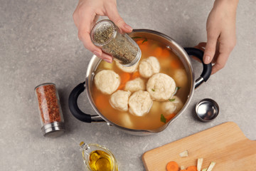 Female hands adding herbs into pan with delicious chicken and dumplings
