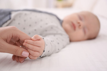 Young woman holding hand of cute sleeping baby, closeup