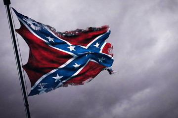 closeup of ripped tear grunge old waving confederate flag of the national states of america us, fabric texture american symbol on cloudy sky, dark mystery style atmosphere